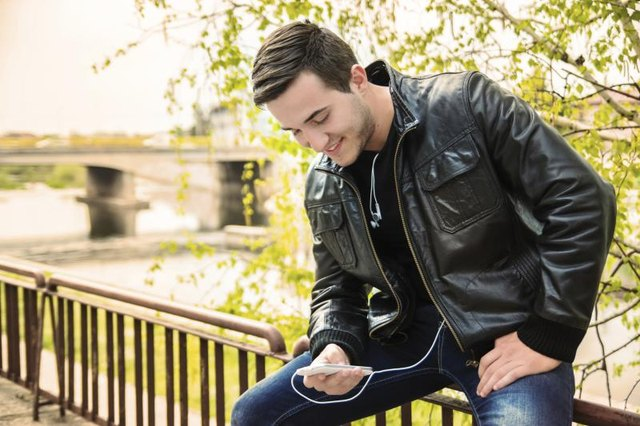 Young man weating a leather jacket, using a smartphone(PhotoAttractive ...