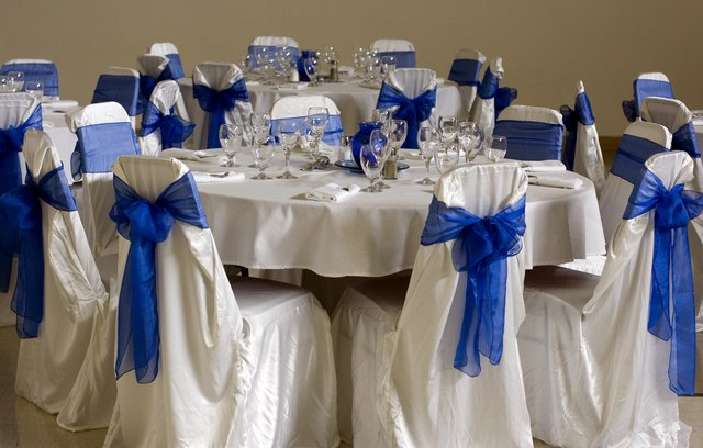 Blue tulle bows are tied around white fabric draped over chairs at a ...