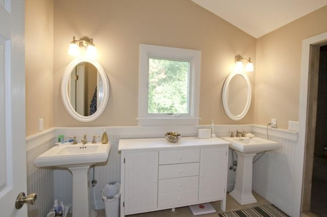 cabinet and window between two porcelain pedestal sinks in a bathroom