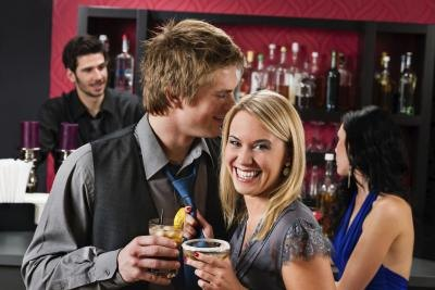 Flirting young couple having drinks at bar candyboximages istock getty
