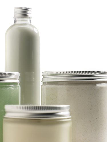 Jars of skin care products on white background