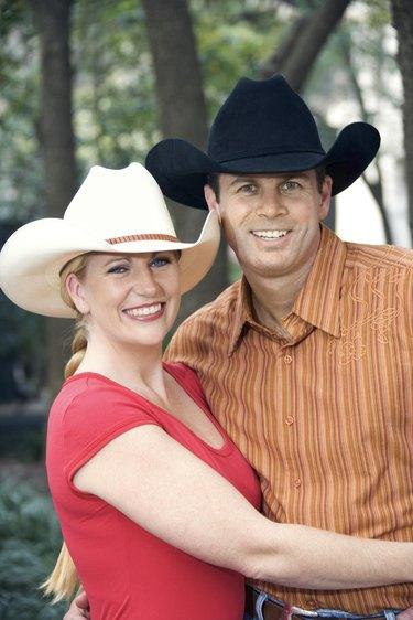 Couple wearing cowboy hats posing outdoors