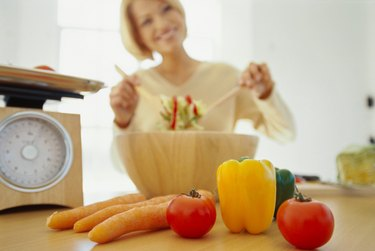 close-up of an array of vegetables on a table with a woman tossing a salad in background