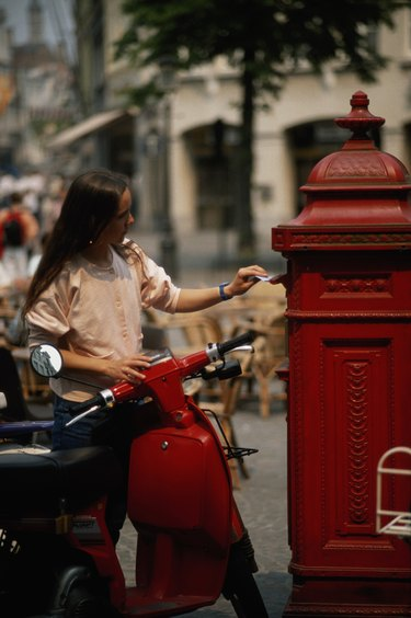 Young woman with motorbike posting letter