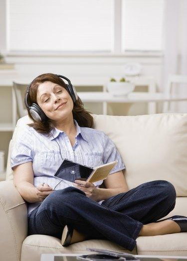 Relaxed woman wearing headphones enjoying listening to music in livingroom