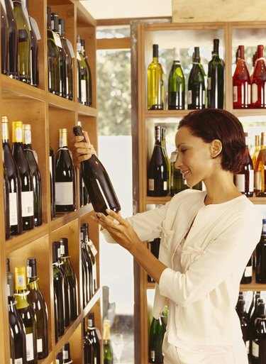 side profile of a young woman reading a label in a liquor store