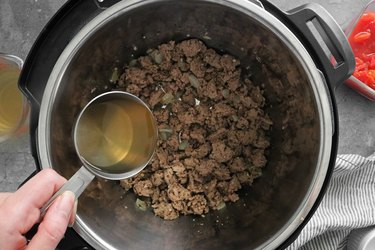 Add broth and scape the pot to prevent burning