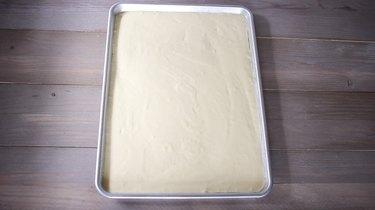 Cake batter poured into large sheet pan