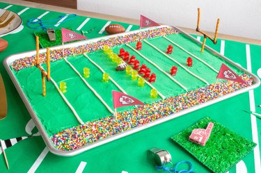 DIY stadium cake on table with whistles and foam finger
