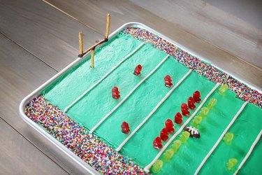 Goal posts made from pretzel sticks inserted into football stadium cake