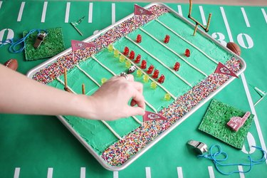 Sticking toothpick flags with team pennants into cake