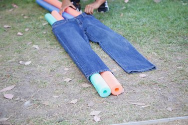 slip pool noodles through jeans legs