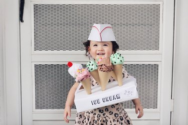 Little girl wearing cardboard ice cream seller costume