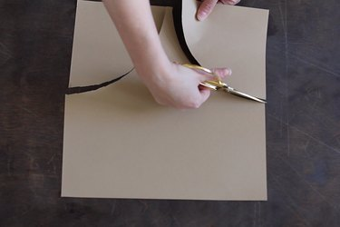 Cutting arc shapes out of brown paper