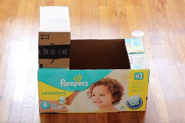 Small box and plastic cup glued on top of diaper box