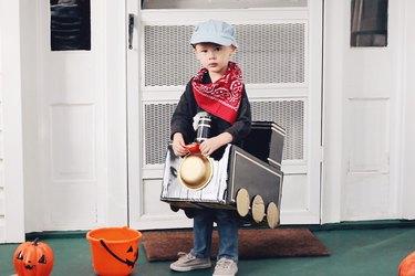 Little boy wearing cardboard train costume