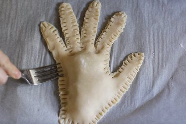 Crimping edges of hand pie with fork