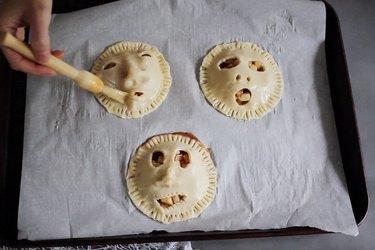Brushing shrunken head pies with egg wash