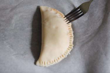 Crimping edges of calzone with fork