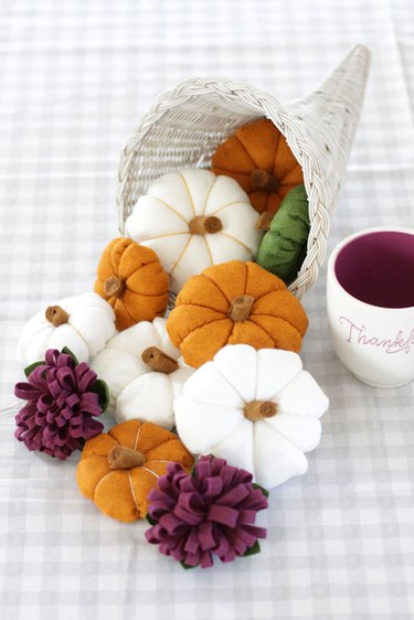 "You can modernize your ""horn of plenty"" centerpiece this season by painting the basket white and creating some delightful felt gourds and flowers to fill it."