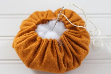 """You can modernize your """"horn of plenty"""" centerpiece this season by painting the basket white and creating some delightful felt gourds and flowers to fill it."""