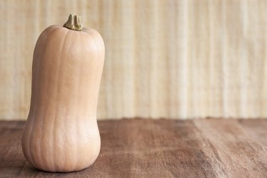 A single whole, uncooked buttercup squash standing upright on a textured brown surface, with a textured beige background