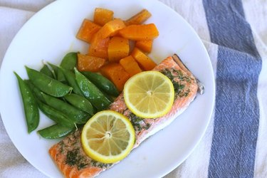 Overhead view of baked salmon topped with herbs and lemon slices, on a white plate with baked squash and snap peas