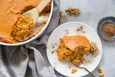 plate of sweet potato souffle with a casserole dish of sweet potato souffle