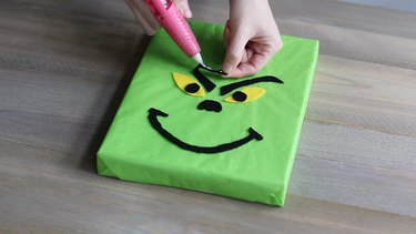 Gluing the Grinch's face features to the box