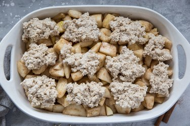 Casserole dish with spiced pears and cobbler topping, ready to go in the oven.