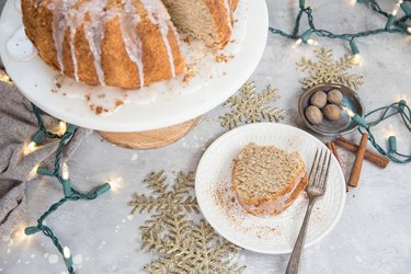 Cake stand with eggnog bundt cake and plate with a slice of cake and a fork