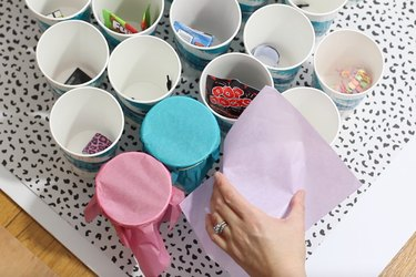 Wrapping tops of cups with tissue paper
