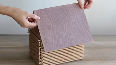 Gluing wood grain paper on top of cake boards