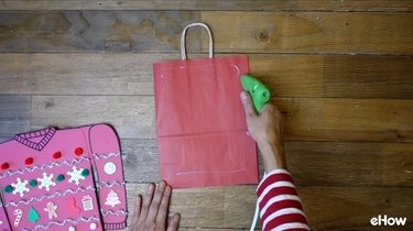 Attaching paper sweater to gift bag.