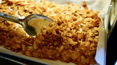 Baking coconut chips to make coconut bacon.