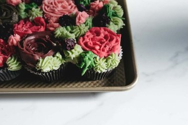 Cupcakes carefully piped with icing to resemble decorative clusters of small succulents and cacti.
