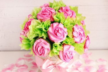 Rose cupcake bouquet against a pale pink background, with a scattering of rose petals underneath.
