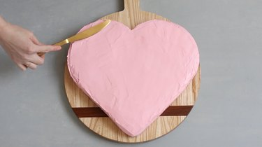 Frosting heart cake with pink icing