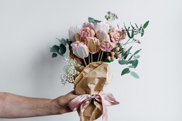 A male hand holding a bouquet of sugar cookies cut and iced to resemble flowers, wrapped in brown paper with stems of real plants to complete the bouquet.