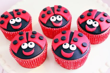 Cupcakes decorated with cutouts of black and red fondant, to give them the appearance of cheerful ladybugs.