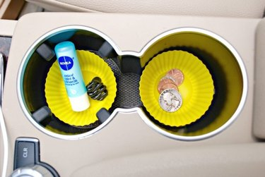 Overhead photo of two bright-yellow cupcake papers in a car's console cup holders, one containing moisturizer and one holding loose change.