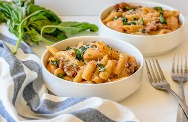 Two white bowls containing pasta, on a white countertop with forks, fresh basil and a kitchen towel.