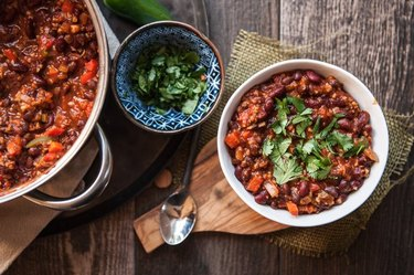 Overhead view of a pot of chili and bowl of chili sitting on separate trivets, with a bowl of chopped green herbs between them.