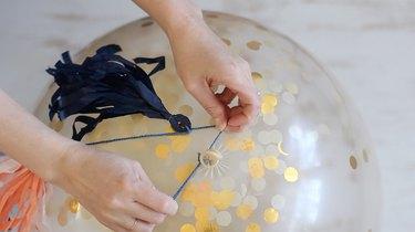 tying tassel garland to balloon