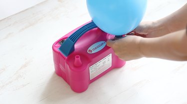 blowing up balloon with pump