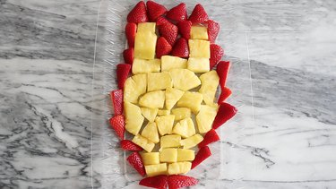 Pineapple and strawberries arranged in Iron Man face shape
