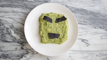 Guacamole in square shape with tortillas forming eyebrows and mouth