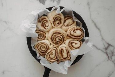 Neatly arrange the cinnamon rolls in the cast iron skillet.