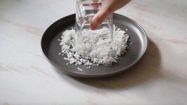 Dipping rim of glass into coconut flakes