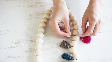 Tying tassels in between wood beads